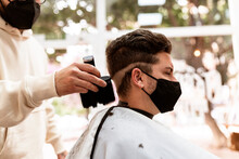 Barber Removing Hair From Cape Of Client In Salon