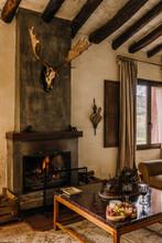 Skull Of Deer Hanging Over Burning Fireplace