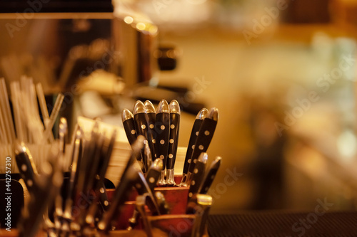 Cutlery stands in a wooden stand in a kitchen, cafe, restaurant, bistro in warm light Fotobehang