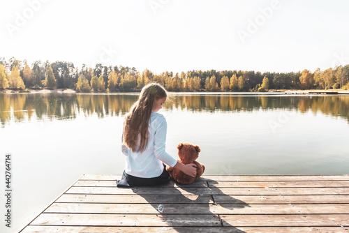 Cuadros en Lienzo Long haired little girl with cute teddy bear sits on pier near wide river agains