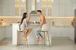 Leinwandbild Motiv Happy couple wearing pyjamas during breakfast at table in kitchen