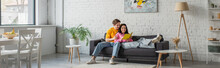Smiling Young Man Hugging Girlfriend Lying On Couch With Book In Hands In Living Room, Banner