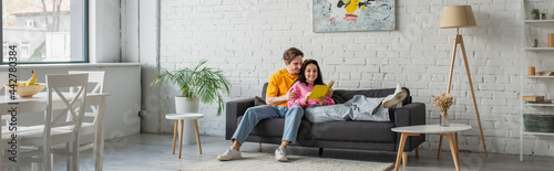 Obraz na plátně smiling young man hugging girlfriend lying on couch with book in hands in living