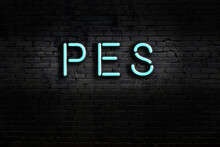 Neon Sign. Word Pes Against Brick Wall. Night View