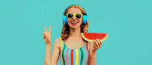 Summer Colorful Portrait Of Cheerful Happy Smiling Young Woman Model Posing In Headphones Listening To Music With Juicy Slice Of Watermelon On A Blue Background