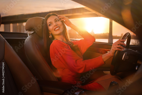Tablou Canvas Sexy woman driving luxury convertible car at sunset
