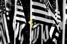 American Flag With A Yellow Ribbon Tied Around The Pole In Black And White.