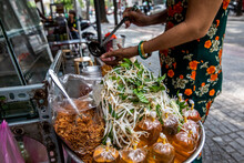 A Street Food Cook Adds Final Condiments To An Entree On Saigon Street