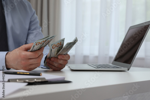 Fotografiet Cashier counting money at desk in bank, closeup
