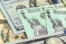 Macro View Of The Statue Of Liberty On A United States Treasury Checks With Currency In Background