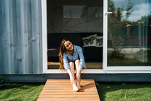 Carefree Beautiful Female Sitting In Front Of Modern Tiny House