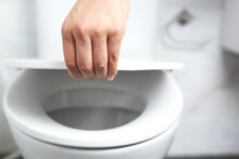 Man's Hand Opening The Toilet Lid