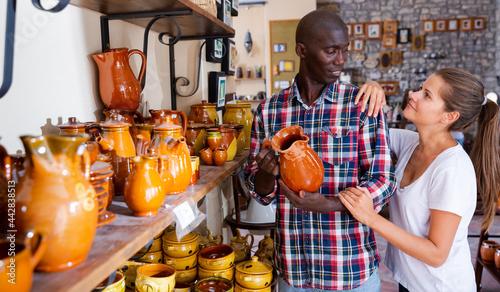 Foto Loving happy couple choosing stoneware in pottery store