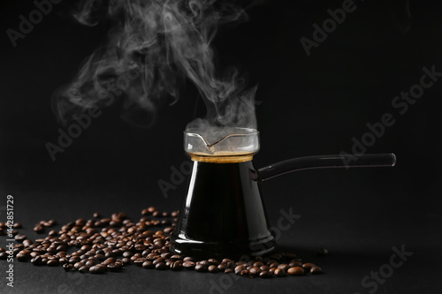 Photo Pot with delicious turkish coffee and beans on dark background