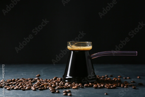 Fototapeta Pot with delicious turkish coffee and beans on dark background