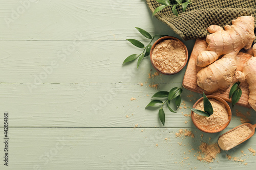 Photo Bowls with ground ginger and roots on color wooden table