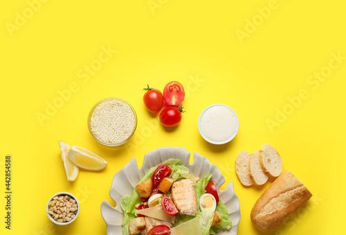 Fotografie, Obraz Plate of tasty Caesar salad and ingredients on color background