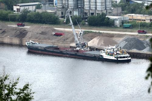 Foto Barge on the river Unloading river sand from a barge Navigable river, river port