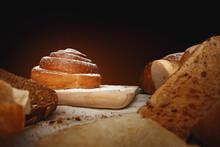 Fresh Cinnamon Bun Roll With Sugar Powder On Wooden Board