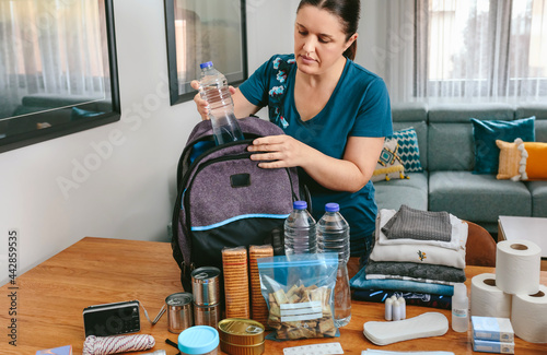 Tela Woman putting a water bottle to prepare emergency backpack in living room