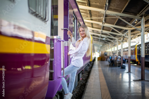 Fototapeta young woman waiting in vintage train, relaxed and carefree at the station platform in Bangkok, Thailand before catching a train