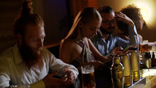 Young Bored People Using Smartphone While Sitting In Modern Bar