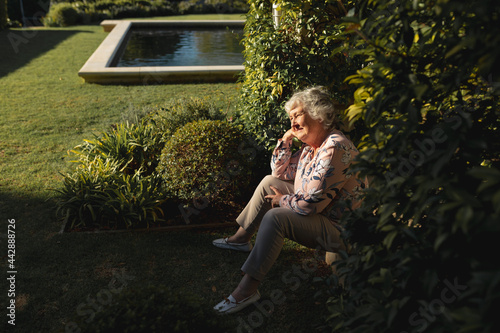 Happy senior caucasian woman sitting and smiling in sunny garden