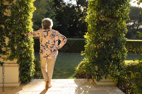 Senior caucasian woman leaning on column in sunny garden