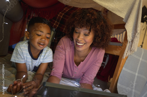 Happy african american mother with son at home, lying in blanket fort and using tablet