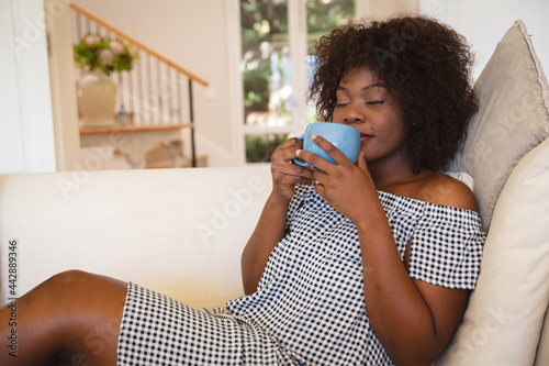 Portrait of smiling african american woman with eyes closed having tea sitting on sofa at home