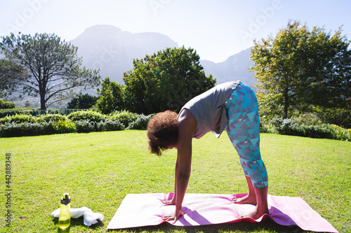 African american woman exercising stretching on yoga mat in sunny garden