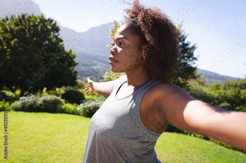 African american woman practicing yoga in sunny garden