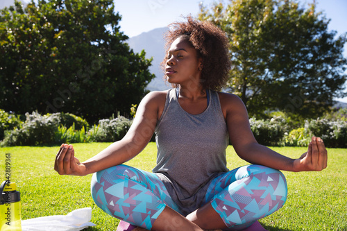 Midsection of african american woman practicing yoga with eyes closed in sunny garden