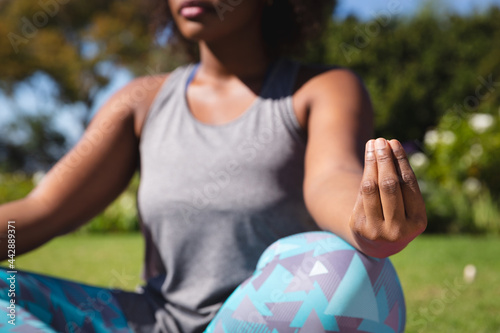 Midsection of african american woman practicing yoga in sunny garden