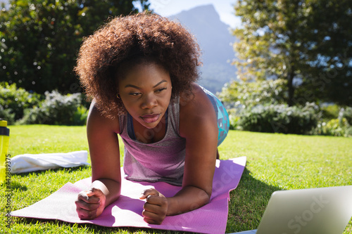 African american woman exercising doing plank on yoga mat in sunny garden