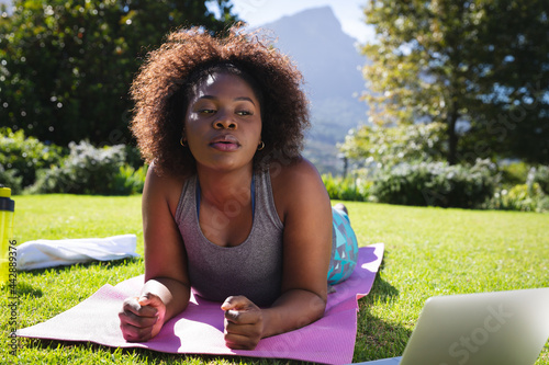 African american woman exercising doing lying on yoga mat in sunny garden