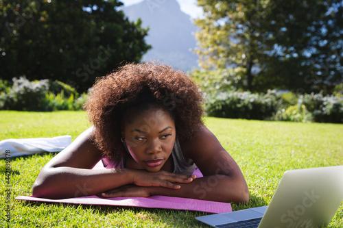 African american woman exercising lying on yoga mat in sunny garden