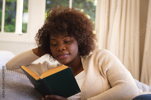 Happy african american woman relaxing in bedroom, lying on bed reading book and smiling