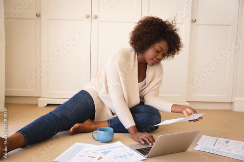 Happy african american woman working in bedroom, sitting on floor using laptop and holding paperwork