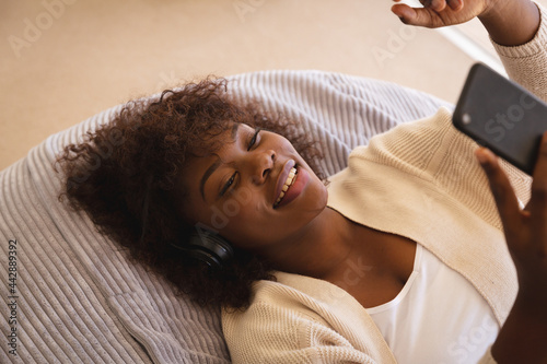 Happy african american woman lying on beanbag making video call with smartphone and smiling