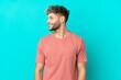 Leinwandbild Motiv Young handsome caucasian man isolated on blue background looking side