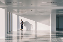 Man Standing In Empty Spacious Office Hall And Browsing Smartphone