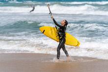Kitesurfer With Kiteboard On Sea Coast In Stormy Weather