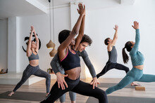 Yoga Instructor Helping Ethnic Black Woman During Group Lesson