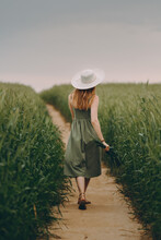Young Woman In A Hat Walking In A Wheat Field, Enjoys Life And Summer. Wheat Field.Healthy Lifestyle Concept
