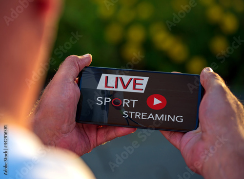 Foto Man watching sport live stream via smartphone in free time