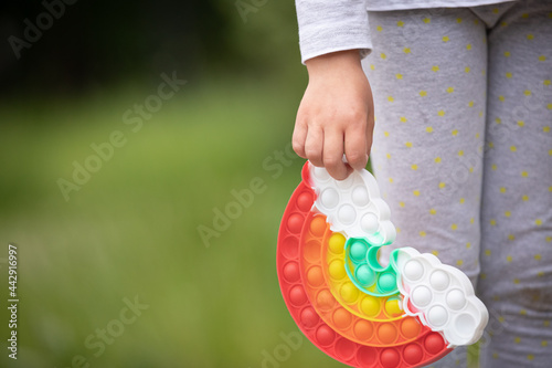 Fototapeta New popular silicone a rainbow colorful antistress toy pop it in the hands of a child