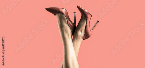 Fotografie, Obraz Pretty female legs with red high heels on red background