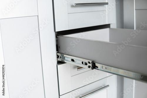 Billede på lærred Stainless telescopic bayonet drawer slide guides, installed on a kitchen cabinet from gray chipboard