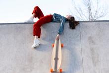 Skateboarder With Longboard Resting On Skate Ramp